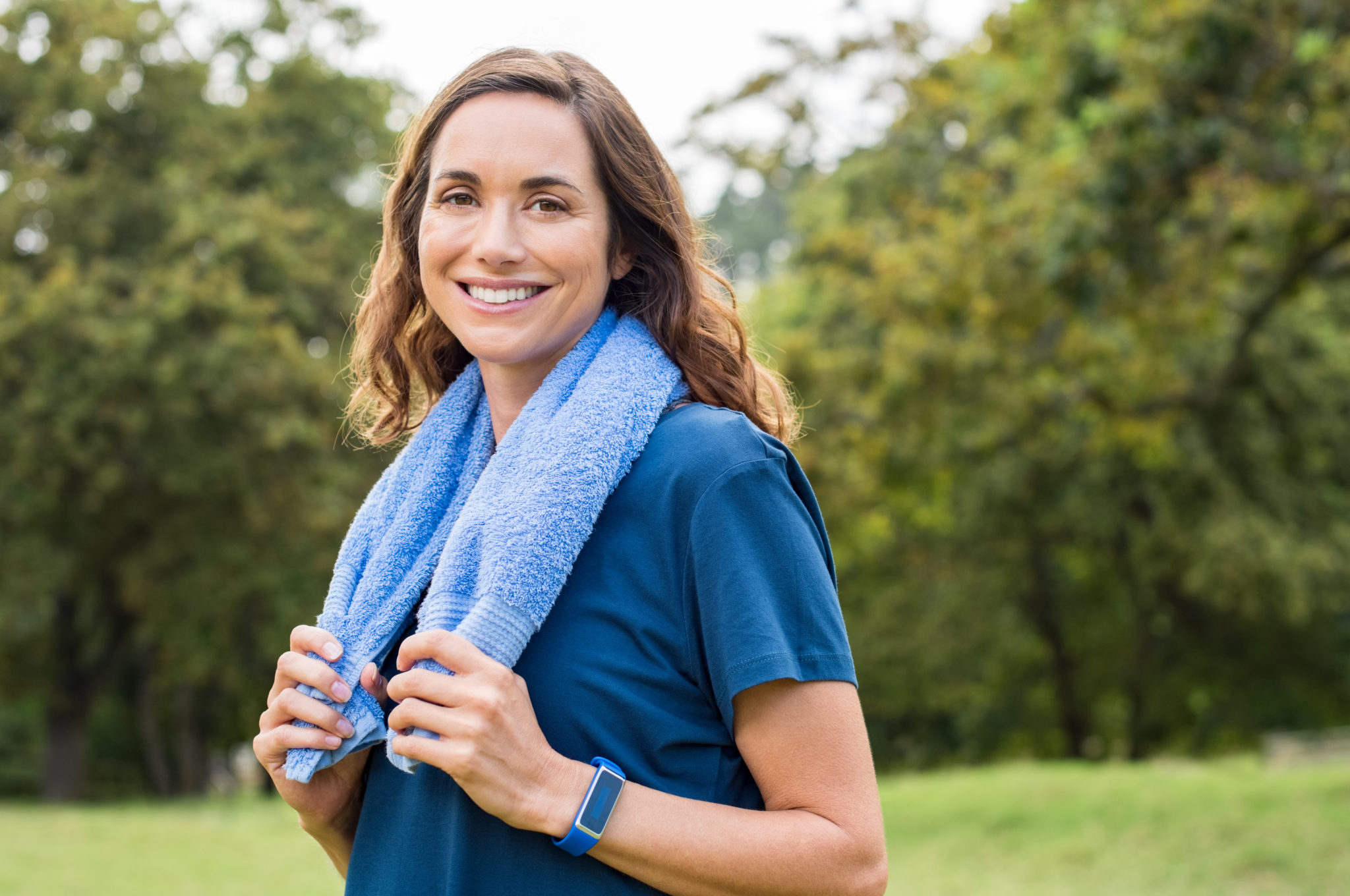 Happy mature woman smiling at park after exercise. Portrait of middle aged woman with blue towel around neck looking at camera. Beautiful mature woman feeling energetic after yoga and exercise outdoor.