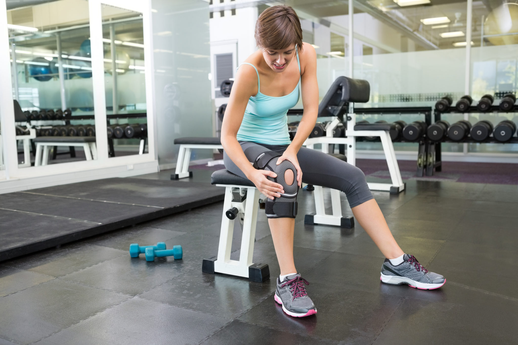 Fit brunette sitting on bench holding injured knee at the gym
