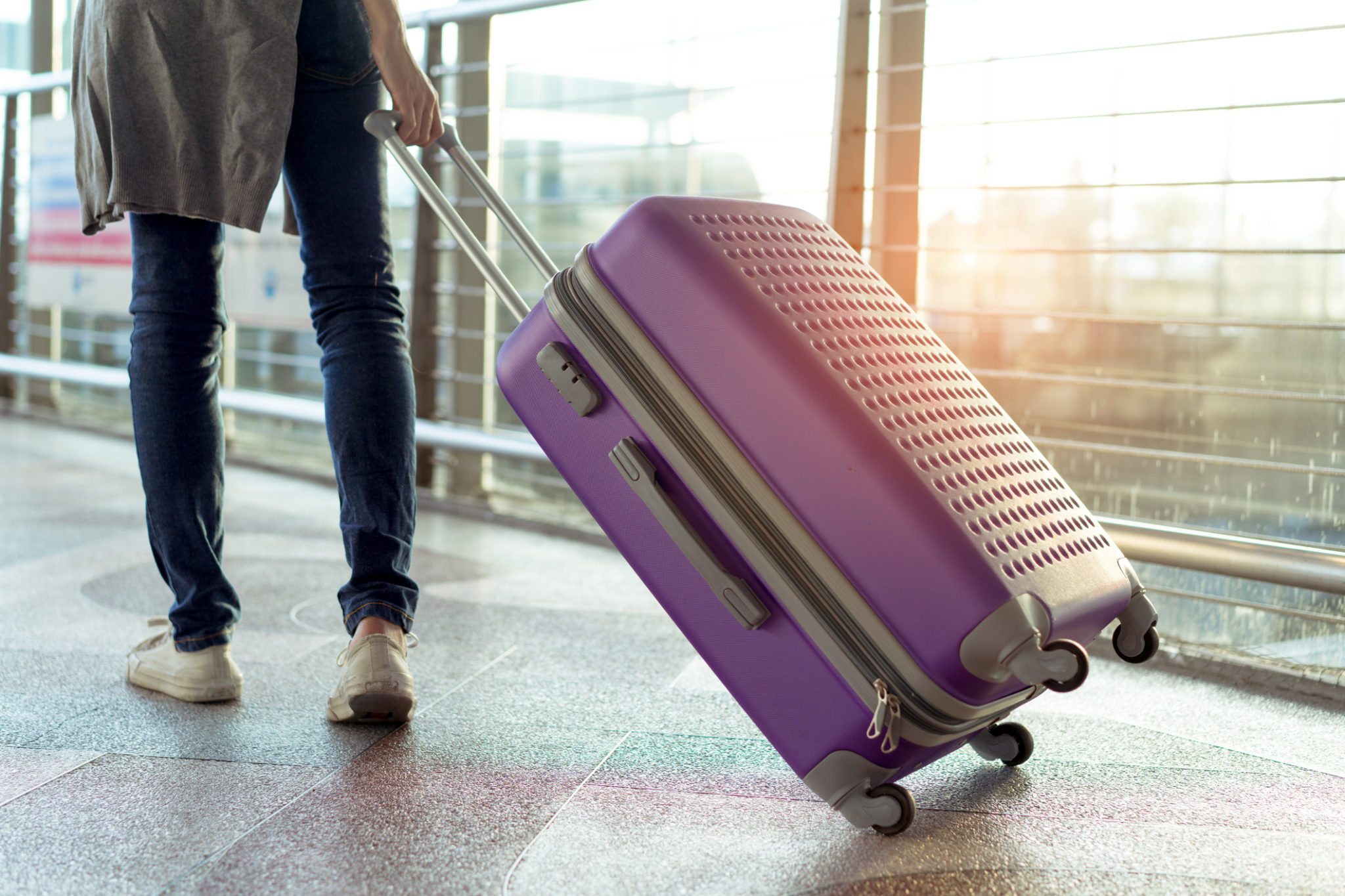 Young girl traveler walking with carrying hold suitcase luggage and passenger for tour travel booking ticket flight in airport international vacation time in holiday rest and relaxation.