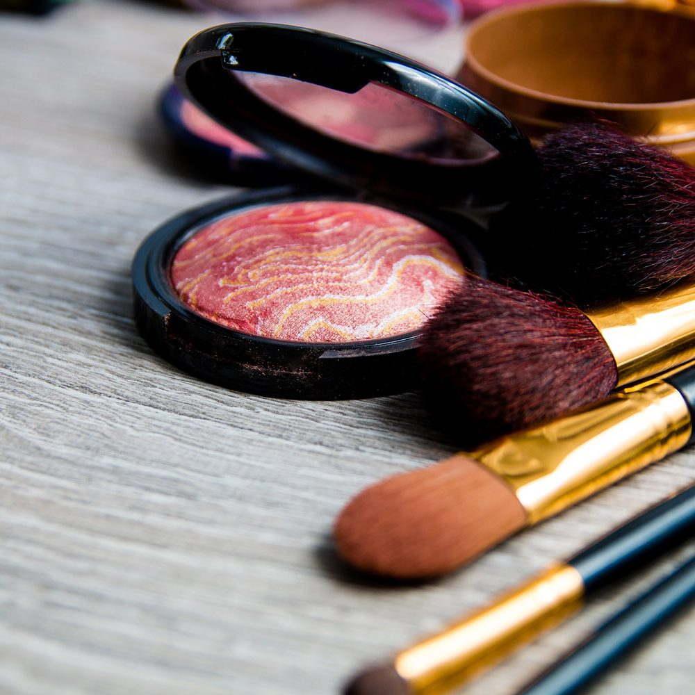 Set of decorative cosmetics and brushes on grey wooden background. Various browns makeup products. Top view, frame. Copy space