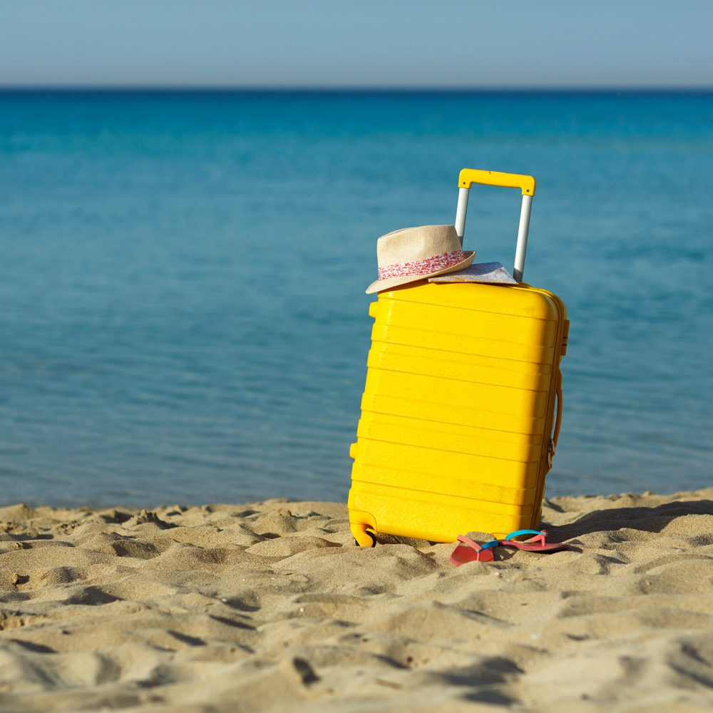 Travel holiday vacation suitcase with map, straw hat and beach slippers on the beautiful sand beach. Advertisement travel suitcase